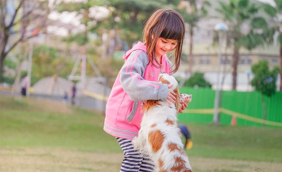 girl with puppy at park